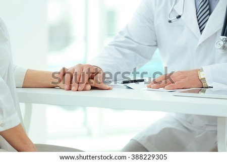 Hands of doctor and patient on table in office - stock photo