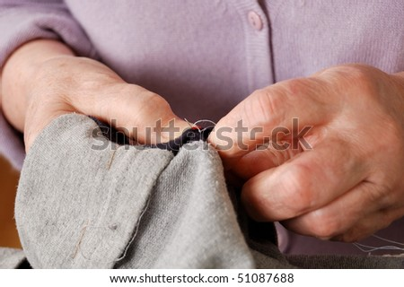 hands of elderly woman repairing the clothes