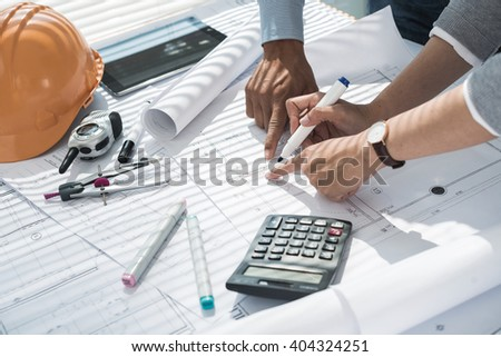 Hands of engineers making corrections in blueprint - stock photo
