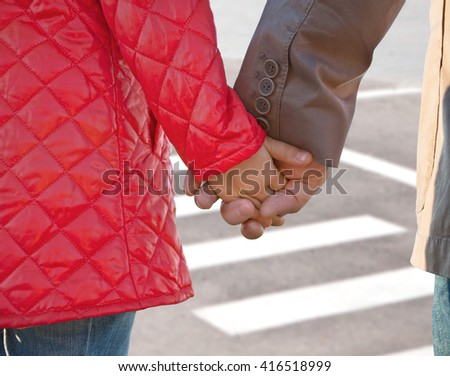Hands of father and child on a pedestrian crossing, close-up - stock photo