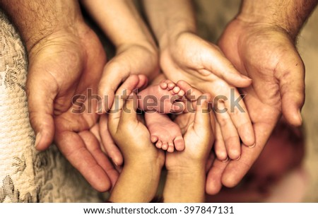 Hands of father, mother, daughter keep little feet baby. Friendly happy family, hands families together - stock photo