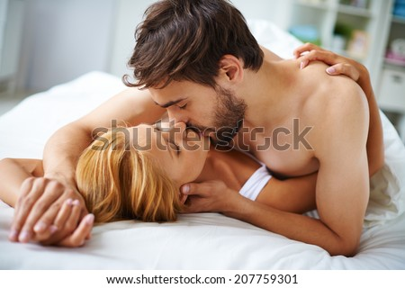 Hands of female and male lying on bed and kissing - stock photo