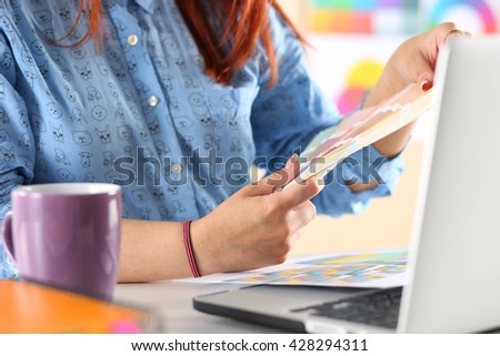 Hands of female designer in office working with colour samples. Woman at workplace choosing colourful paper charts. Creative people or advertising business concept - stock photo