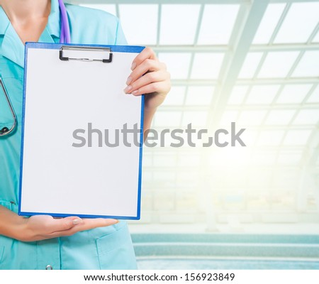 hands of female doctor holding clipboard - stock photo