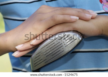 Hands of female golfer resting on the club-head, a three wood