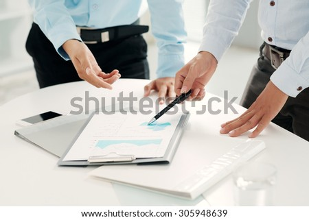 Hands of financial managers analyzing business document - stock photo