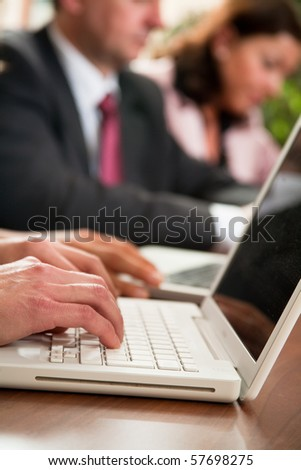 Hands of four business people working at meeting - stock photo