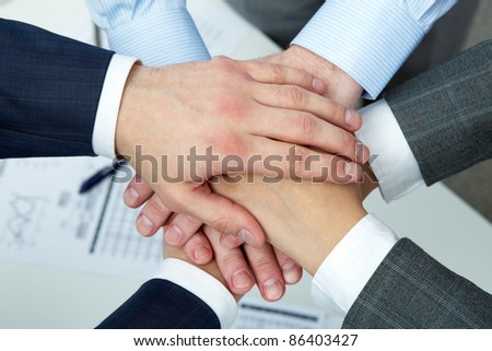 Hands of four businesspeople on top of each other - stock photo