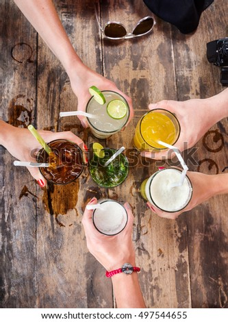 Hands of friends together in circle holding the different cocktails with ice on background of the old wooden table surface. View from top