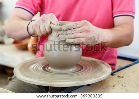 Hands of greek ceramic master and his disciple  during clay workshop. Closeup shot of hands making clay jar - stock photo