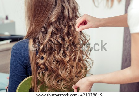 Hands of hairdresser braid straight long hair on  background of a barber