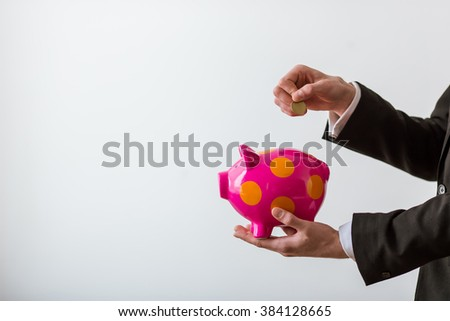 Hands of handsome young businessman in classic suit holding a piggy bank and coin, on white background - stock photo