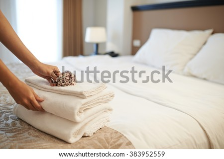 Hands of hotel maid putting flowers on the stack of towels - stock photo