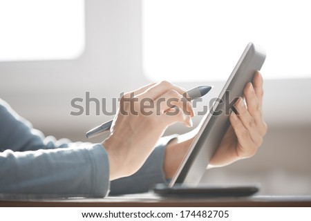 Hands of human using digital tablet and stylus