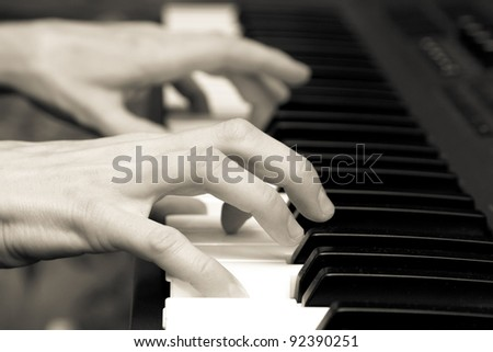 hands of keyboard player on keys of synthesizer. black and white - stock photo