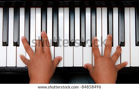 Hands of kid on piano keyboard - stock photo