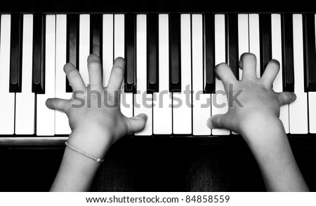 Hands of kid on piano keyboard in black and white - stock photo