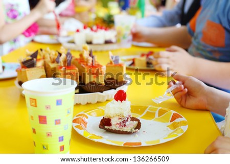 Hands of kids eating delicious little cakes on yellow table. Focus on cake. - stock photo
