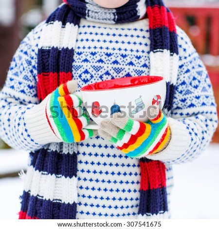 Hands of little child holding big cup with snowflakes and hot chocolate drink and marshmallows, outdoors with snow background. Kid boy in winter sweater, hat, long warm scarf and colorful gloves.  - stock photo