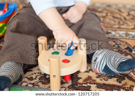Hands of Little toddler boy playing with wooden toys indoor - stock photo