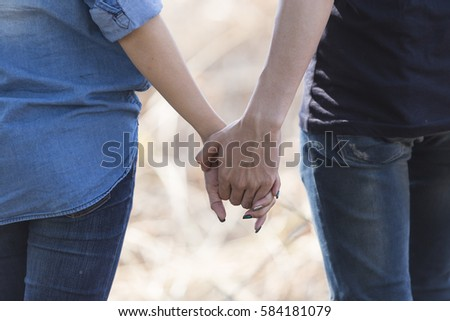 Hands of  Love couple walking hand in hand on the road,forest and mountain,Romantic couple in love holding hands on the travel,Young couple in love, Attractive man and woman enjoying romantic evening.