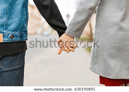 Hands of lovers. Couple walking in the city holding hands.