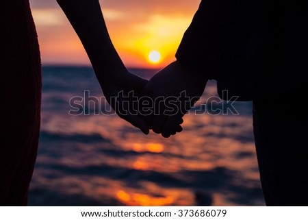 Hands of lovers man and woman on the background of sunset on the sea