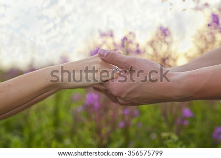 hands of lovers on a summer background - stock photo