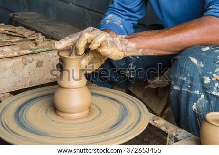 Hands of making clay pot on the pottery wheel.  Ban Tha Hai in Ubonratchathani, Thailand ,select focus, close-up. - stock photo