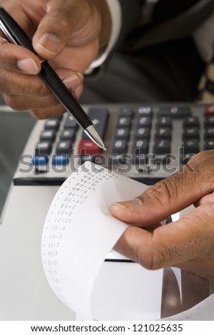 Hands of male accountant with calculator paper tape - stock photo