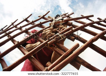 Hands of male builder. Man builds Asian yurt frame. Nature House construction  - stock photo