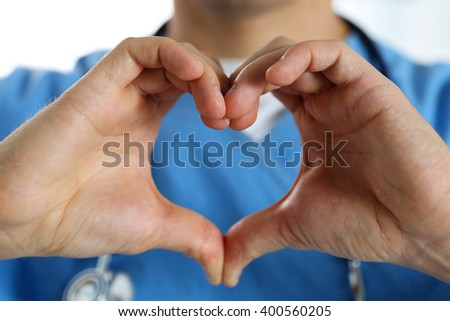 Hands of male medicine therapeutist doctor wearing blue uniform showing heart shape closeup. Cardio prophylaxis or insurance, protection and prevention, healthy heart, eating and life style concept - stock photo