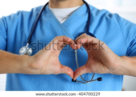 Hands of male medicine therapeutist doctor wearing blue uniform showing heart shape closeup. Cardio prophylaxis, physician make cardiac physical, healthy heart, pulse rate measure, arrhythmia concept - stock photo