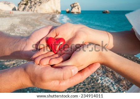 Hands of man and woman holding red heart on beautiful sea background at Aphrodite's legendary birthplace