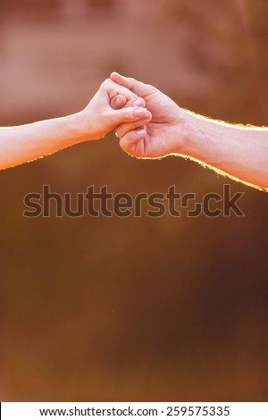 Hands of man and woman holding together outdoor - stock photo