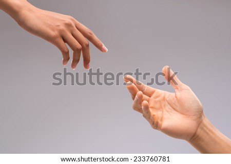 Hands of man and woman reaching to each other - stock photo