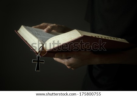 Hands of man holding holy bible and wooden rosary - stock photo