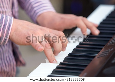 hands of man in a striped shirt play the piano jazz - stock photo