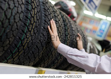 hands of man or woman touching & choosing for buying a tire in a supermarket mall - stock photo