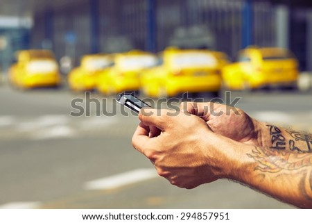 Hands of man ordering taxi, using mobile phone app - stock photo
