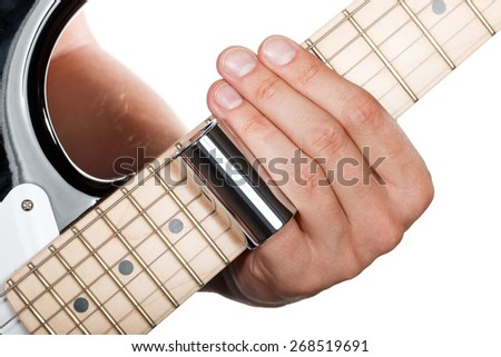 Hands of man playing electric guitar. Guitarist hands. Fingers with metallic slider pressing strings on maple fretboard closeup - stock photo