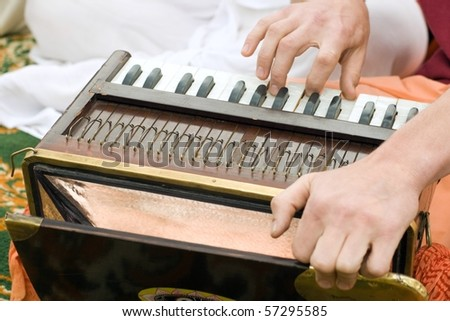 Hands of man playing mantra on accordion - stock photo