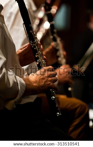 Hands of man playing the clarinet in the orchestra in dark colors