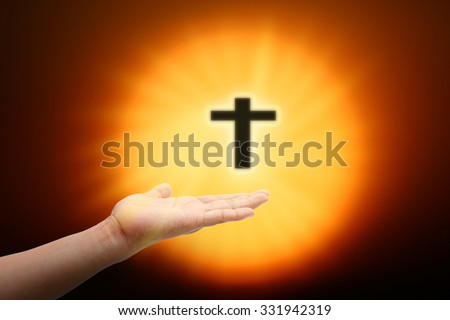 Hands of man praying and the blurred cross on a sunset.