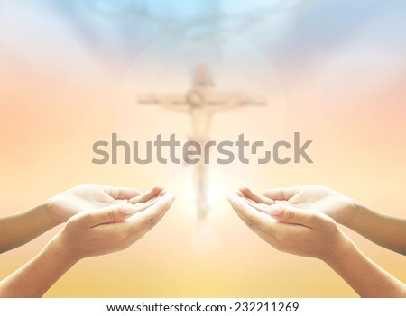 Hands of man praying over blurred crown of thorns and Jesus on the cross over a colorful sunset. - stock photo