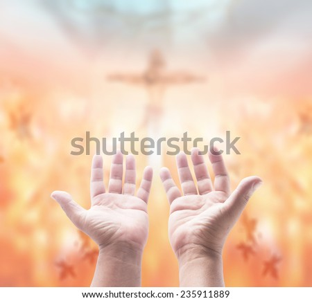 Hands of man praying over blurred crown of thorns and Jesus with the cross on a sunset. - stock photo