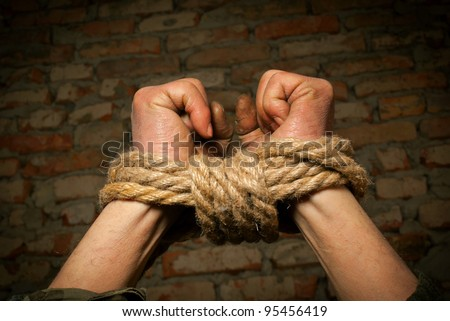 Hands of man tied up with rope against brick wall - stock photo
