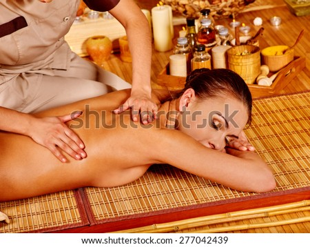 Hands of masseur doing massage young woman in bamboo spa. - stock photo