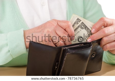 hands of mature woman holding wallet with money - stock photo
