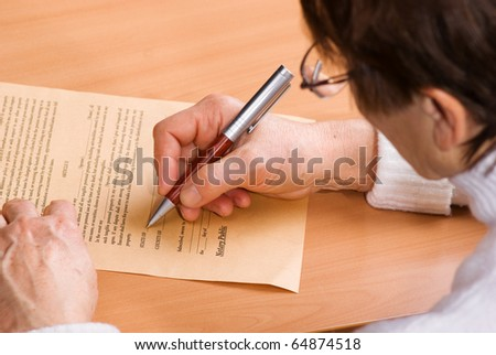 Hands of mature woman signature document sitting on desk - stock photo